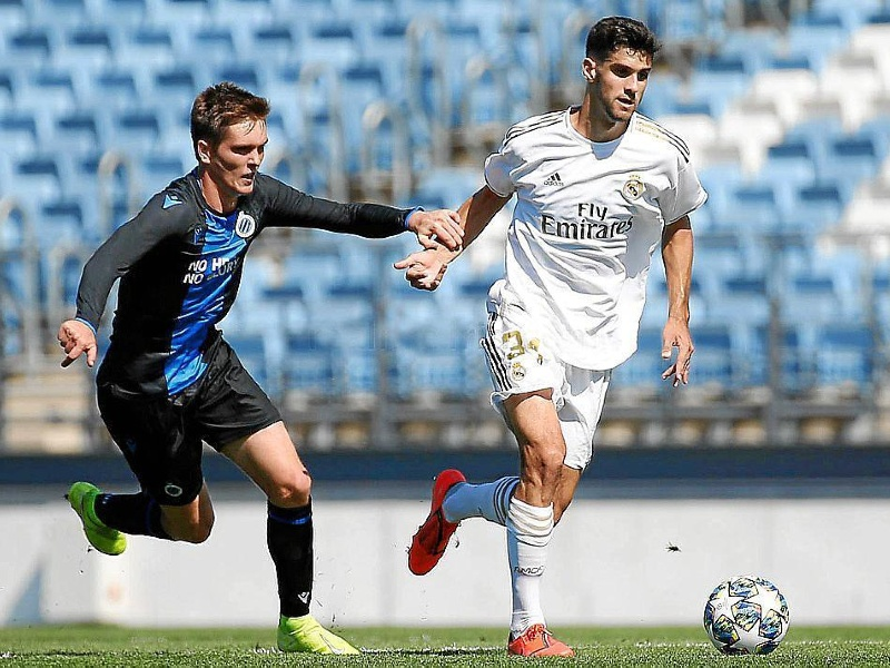 Real Madrid player Xavi Sintes holds off Club Brugge player